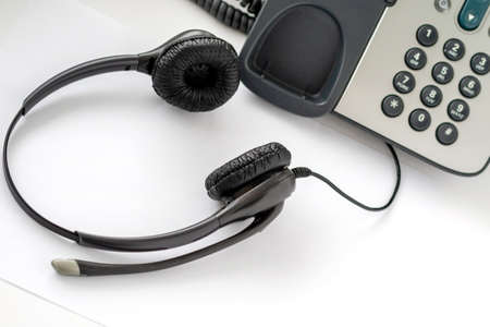 headset for a traditional call center employee push-button telephone, light background