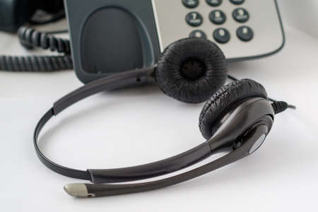 call center employee workplace, traditional push-button telephone and headset, close-up shot of headphones