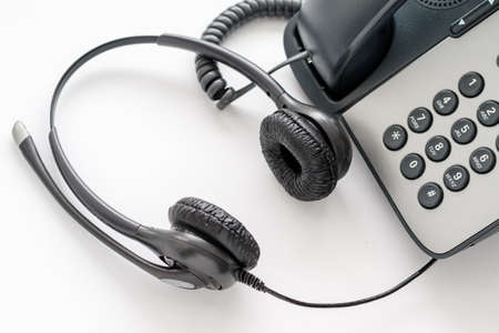 Close-up of a headset lying by an old push-button telephone. call center employee workplace