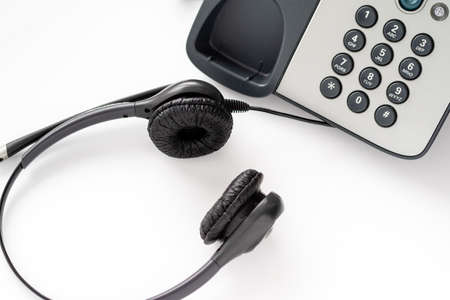 Wired headset at a push-button telephone. working hours of a call center employee