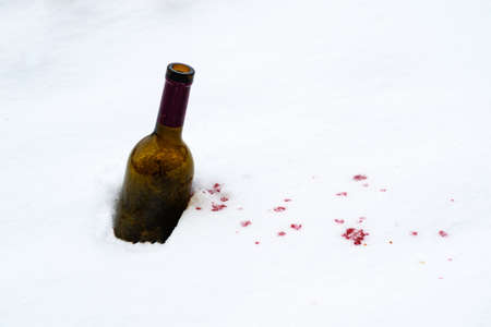 a bottle of wine in the snow red wine spilled out of it onto the snow. red spots on white snow