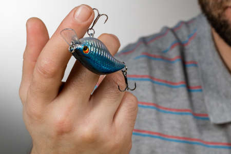 fishing lure stuck in a mans finger. background gray blurred