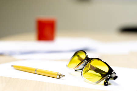 yellow fountain pen and glasses for yellow vision on a white table. writer workflow