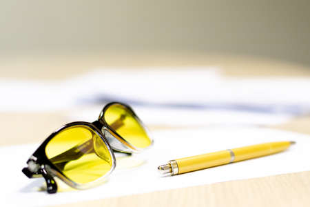 yellow glasses for working on a computer are on the table next to a fountain pen. oyayas employee break