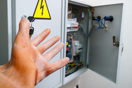 hand in a dielectric glove on a background of an electrical panel. the concept of safe operation in electrical installations