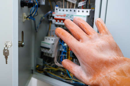 a hand in a dielectric glove opens the door to the electrical panel. compliance with safety measures when working in electrical installations 版權商用圖片