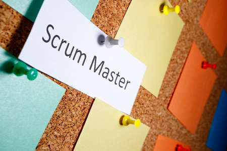 Scrum master is written on a piece of paper which on a bun is attached to a board. outgoing perspective view