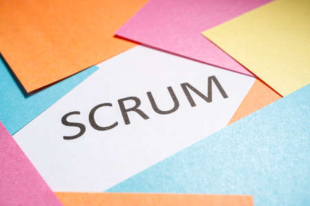 Scrum is written on white paper around which colored papers are located. perspective view from below not all inscription in sharpness