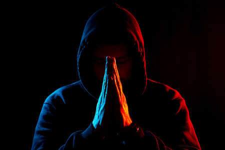 a man in dark clothes in a hood on a dark background folded his hands for prayer. different types of lighting from different sides simolize fire and ice