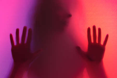 the girl's arms and torso are illuminated through the fabric from the other side. mysterious stranger with different colors of lighting