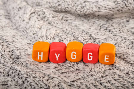 hygge is written on plasticine cubes placed on a knitted surface. comfort and coziness