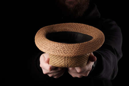 a hat stretched out of the dark for begging money. request for help with money