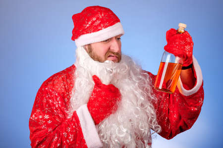 a man in a santa claus suit pulls his beard off his face and looks at the bottle wow in his hand. you can finally have a drink after the holidays