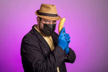 a man in a mask and a hat holds a banana in his hands like a gun. banana killer