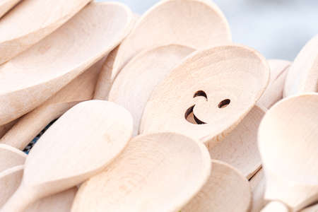 from many identical spoons made of wood, one with a smile. eye catching spoon Stock fotó
