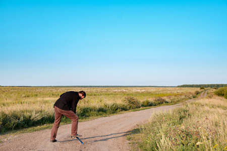 a man in with a shovel digs a road running in a field. that would not have driven uninvited guests