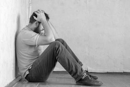 a man with a beard is sitting in the corner of the room with his head in his hands. being at home in self isolation the man began to feel depressed