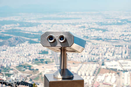stationary binoculars for long-range observation mounted on a hill. summer day in the city out of focus Banque d'images