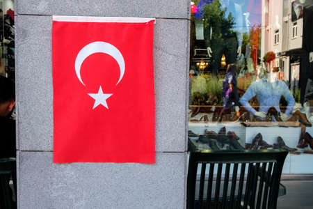 the flag of Turkey is vertically located on the column of the building background vertina. trade in Turkey is booming