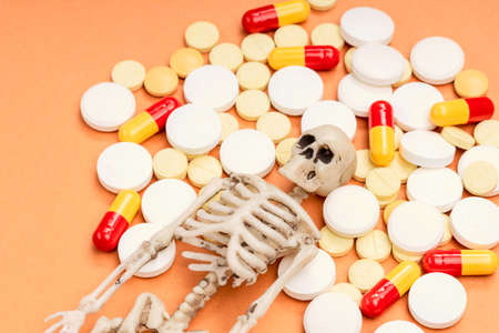 human skeleton and many pills next to it. pill overdose