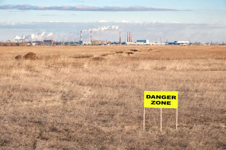 sign on the field with dry grass in front of the plant, the inscription is a danger zone. environmental problem
