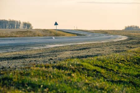 turn on the road, grass grows on the side of the road. evening on a country road