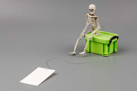 a skeleton sitting on a box in his hand with a thread to which a fish hook with empty paper is attached. place for the inscription death catches on promises
