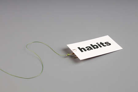 white card with the inscription hobby is attached to a fishing hook. addiction to your hobby