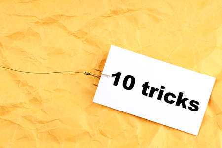 paper on a fishing hook with 10 tricks written on it. tricks for people