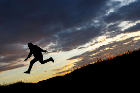 silhouette of a man running downhill on the background of sunset. running away from problems