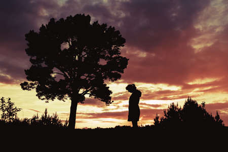 silhouette of a woman standing by a tree outdoors against a sunset background. sadness and depression of an odd woman