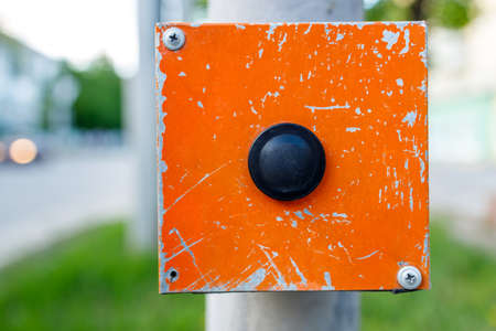 iron box on a support with a button for crossing a pedestrian crossing. click on the button to get the result