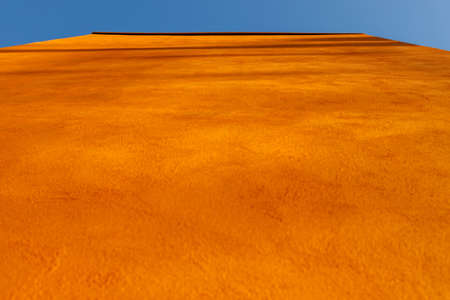 the wall of the building extending upward in orange, viewed from below