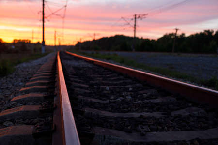 railway rails during sunset with reflections on the metal. rails going into the distance