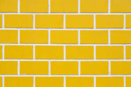 a wall with yellow artificial bricks, a decorative wall of a corded brick and a white space between them