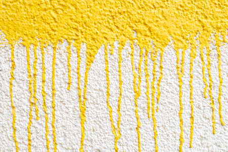 drips of yellow paint on a white wall, drops down. wall painted yellow and white