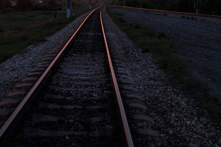 the rails on the railway tracks are illuminated by the setting sun during sunset. railway tracks going into the distance