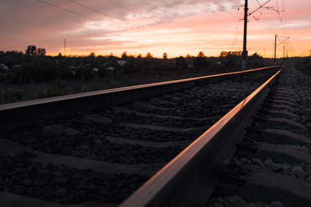 shiny rails extending into the distance during sunset. landscape on the railway road the beginning of the path