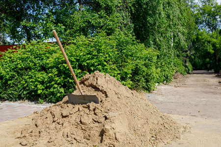 there is a mountain of sand on the sidewalk, a shovel is inserted into it, road repair Stock fotó
