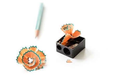 pencil and sharpener on a white sheet of paper, shallow depth of field. shavings on a sharpener in the form of a flower