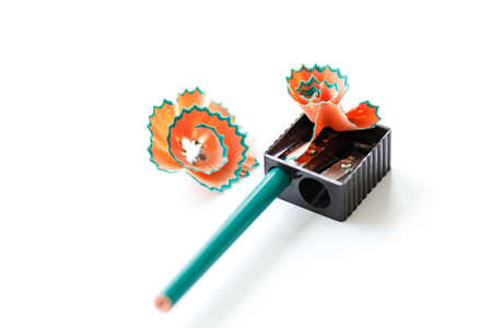 pencil sharpener with shavings on white sheet of paper, pencil sharpening process