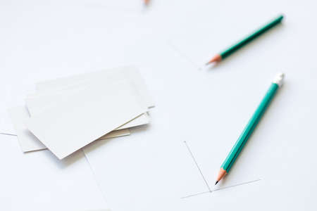 blank business cards and a white sheet of paper containing two pencils