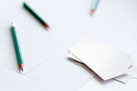 white business cards on a white sheet of paper, two pencils side by side and the beginning of the diagram drawn in pencil. Beginning of work