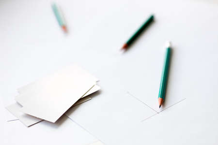 beginning drawing on a sheet of white paper and blank business cards. pencils out of focus Stock fotó