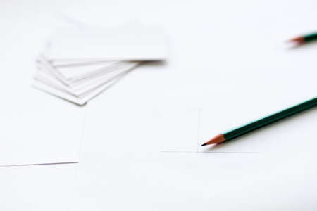 pencil close up on foreground, background out of focus blurred business cards
