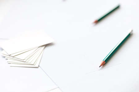 two pencils on white paper, the beginning of the drawing, and white blank business cards. work but abandoned Stock fotó