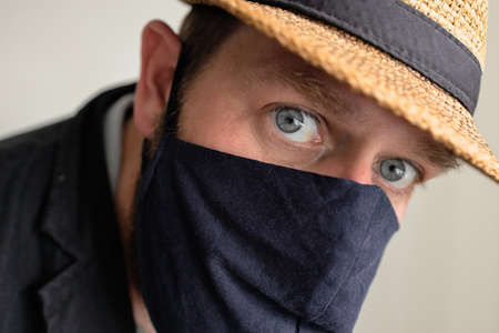 an adult man in a mask looks closely into the frame, a hat is on his head Stockfoto