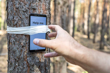 a phone is tied with tape to a tree trunk in the forest, it says save me, a hand reaches for it. someone needs help he got lost in the forest