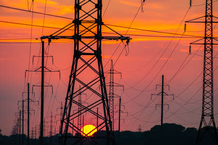 power poles against the setting sky and a large sun. wires through which electric current flows horizontal photo
