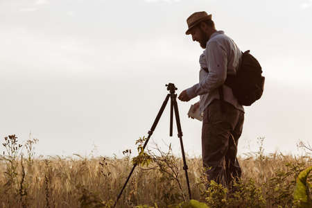 a surveyor with a beard set up a tripod on the field. man keeps records of agricultural holdings